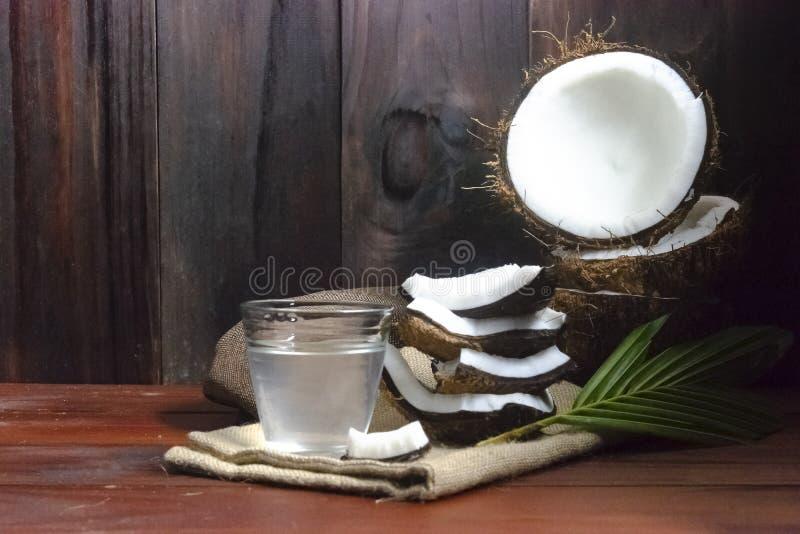 Metade do suco da água do coco ou do coco e do coco e partes e folha do coco na tabela de madeira e no fundo de madeira preto imagem de stock