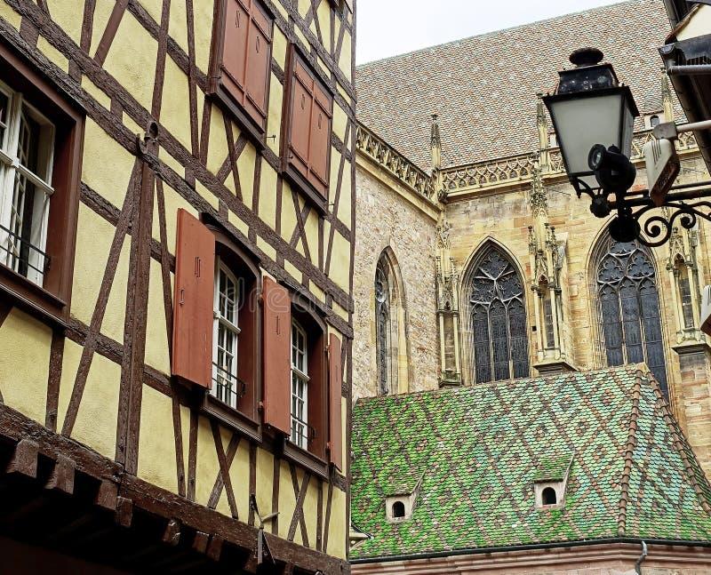 A metade suportou a casa e a igreja com o telhado de telha modelado bonito - Colmar, França imagem de stock