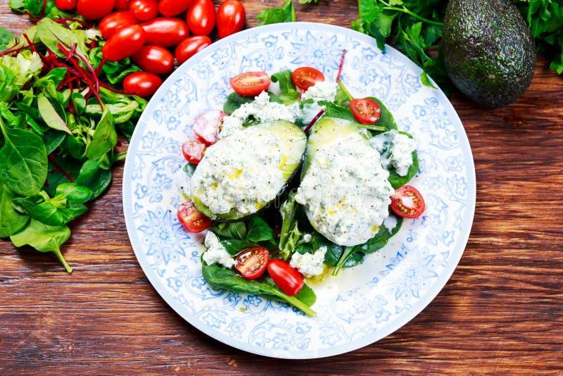 Metades do abacate enchidas com requeijão e vegetais imagem de stock royalty free