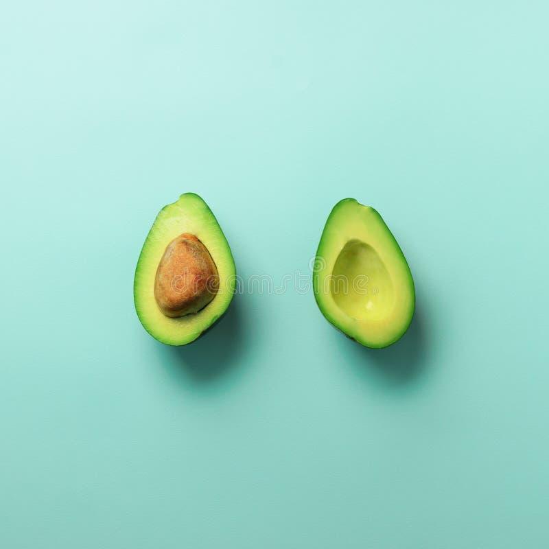 Metades verdes do abacate com a semente no fundo pastel azul O plano mínimo criativo coloca o estilo com espaço da cópia Alimento imagens de stock royalty free