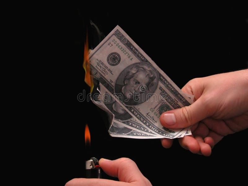 Metafora: Soldi da bruciare fotografia stock libera da diritti