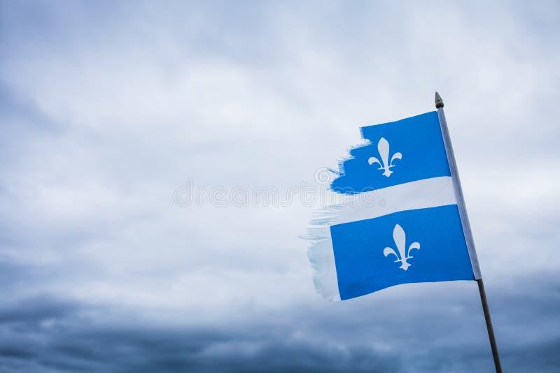 Metafora używać Łamaną Quebec flaga i Smutnego niebo obraz royalty free