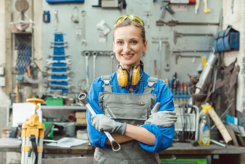 Metalúrgica feminina com uma posagem de ferramenta para a câmera imagens de stock royalty free