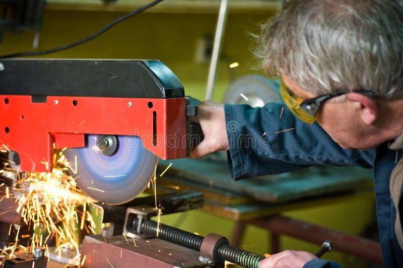 Metalúrgico que corta el metal con la sierra rotatoria imagenes de archivo