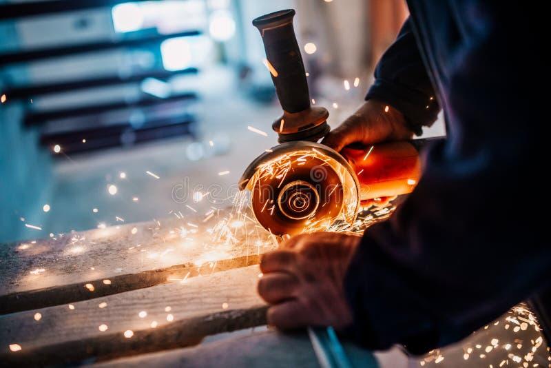 Metalúrgico que corta o ferro e o metal com um moedor e um trabalho giratórios elétricos de ângulo, gerando faíscas de metal imagem de stock