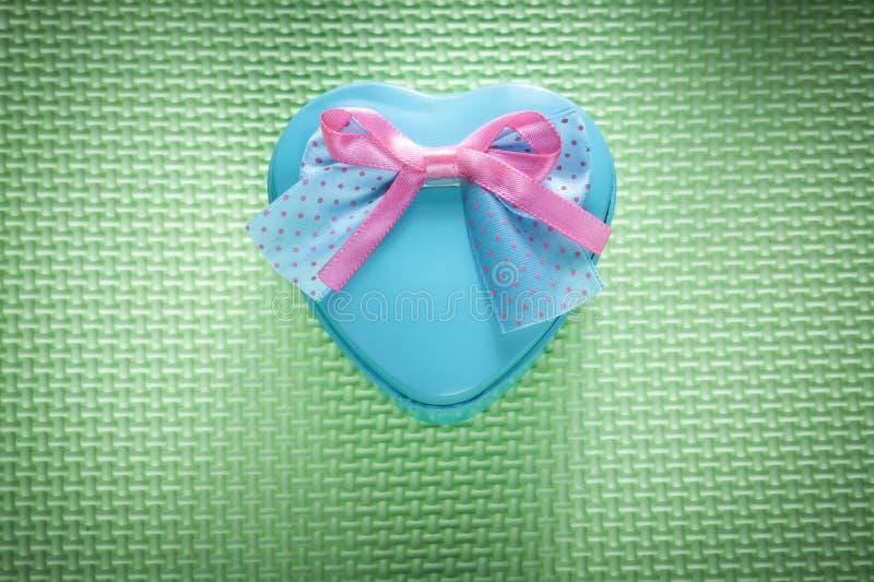 Metal голубая в форме сердц присутствующая коробка на зеленых поверхностных праздниках co стоковое изображение rf