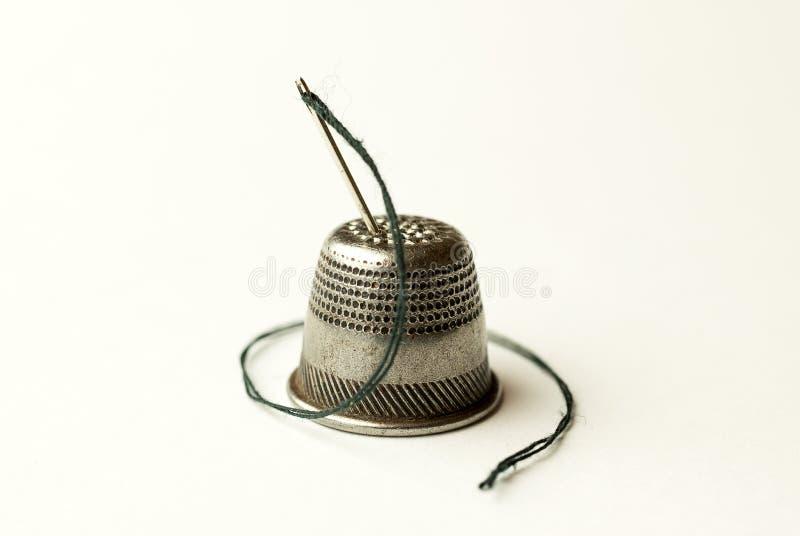 Metal кольцо и игла с потоком на белизне стоковое фото
