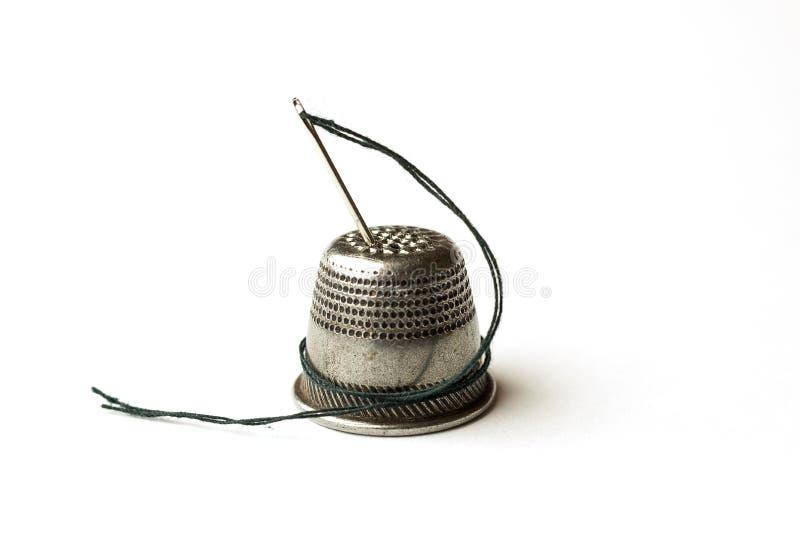 Metal кольцо и игла с потоком на белизне стоковые фотографии rf