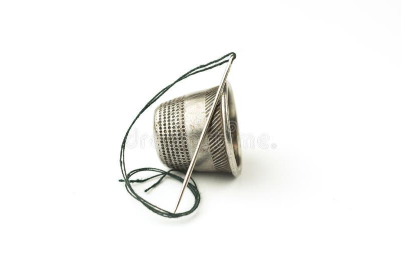 Metal кольцо и игла с потоком на белизне стоковое изображение