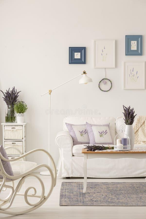 Metal лампа помещенная софой в реальном фото белого интерьера живущей комнаты в провансальском стиле с свежими лавандой и плаката стоковая фотография rf