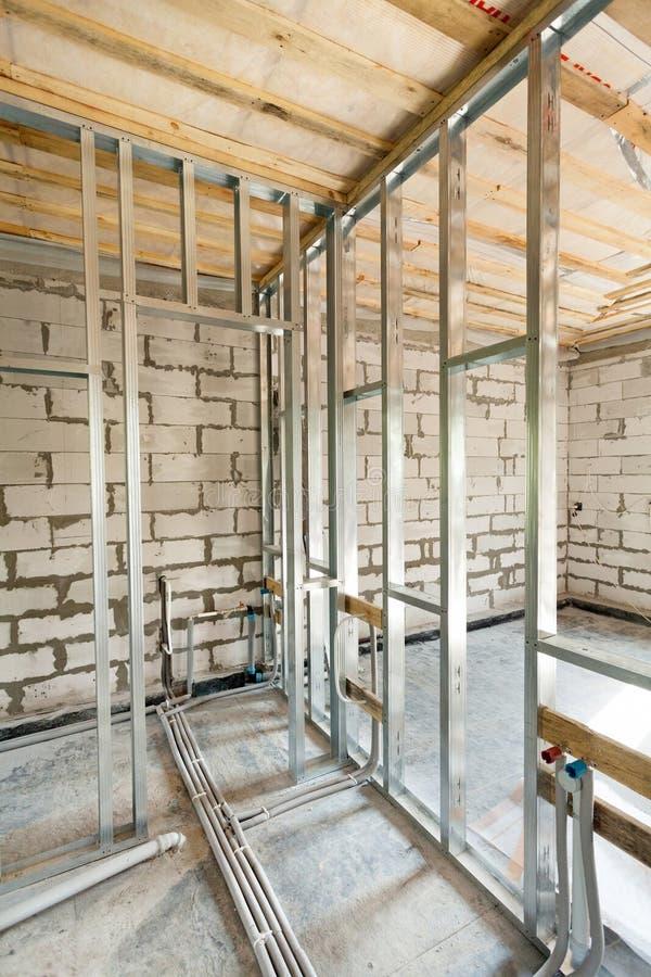 Metal рамка профиля для стен и труб штукатурной плиты с клапанами системы отопления в доме стоковое фото