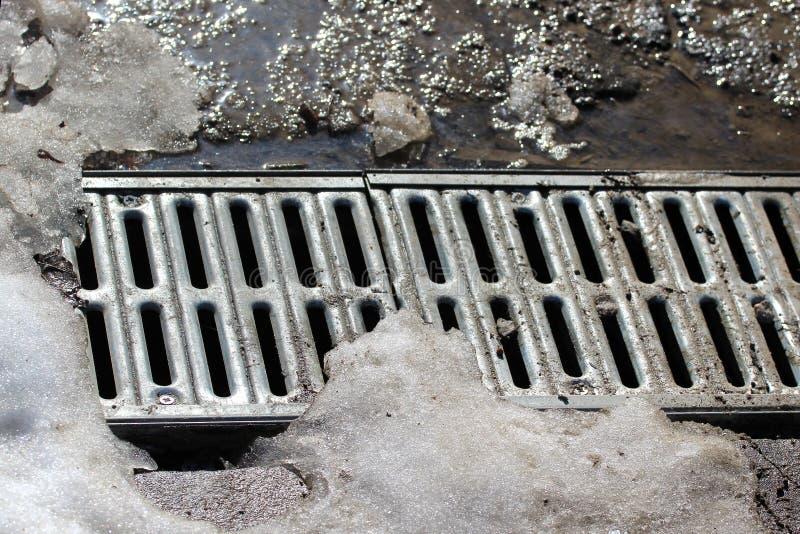 Metal решетка дренажа воды под плавя снегом стоковые фотографии rf