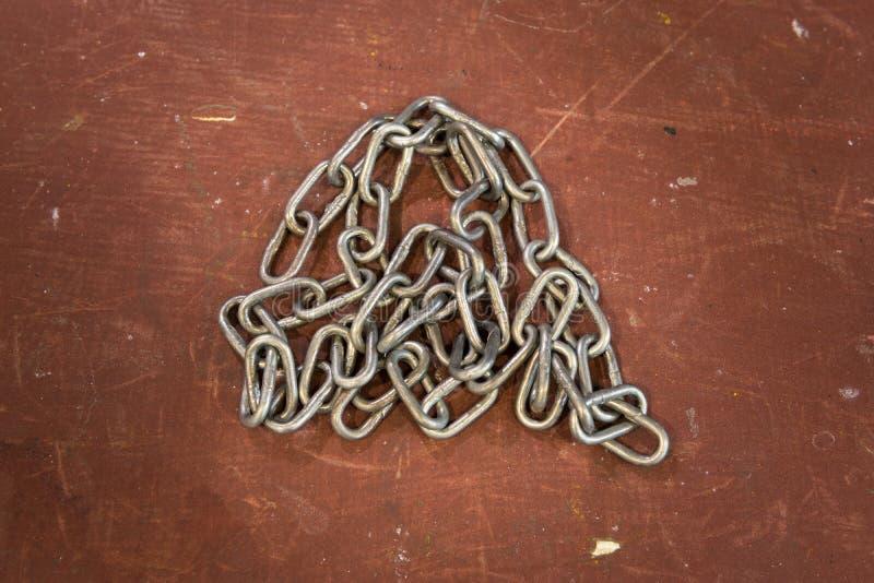 Metal серебряная цепь против грубой и поцарапанной красной предпосылки, поверхности Промышленные обои стоковые изображения rf