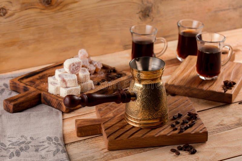 Metal турок и кофейные зерна на кофе деревянной предпосылки турецком в традиционный выбитый турка металла стоковая фотография