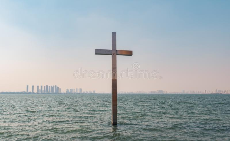Metal христианский крест в воде над предпосылкой голубого неба стоковая фотография rf