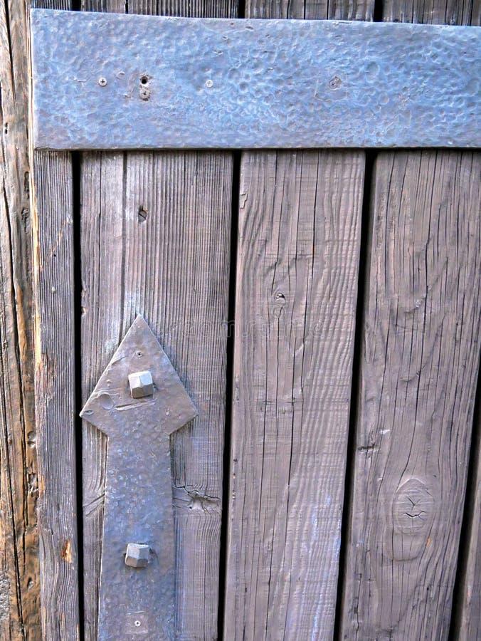 Metal шарнир с формой стрелки указывая налево над старой деревянной дверью стоковое фото
