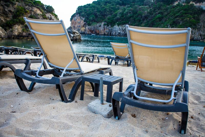 Metal Adjustable Recliner Along Shoreline Facing the Ocean. Blue Beach Furniture on Fine White Sand. Green Cliffs and. Crystal Blue Water in the Background royalty free stock image