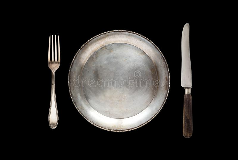 Metal antique plate, knife and fork isolated on a black background royalty free stock photos