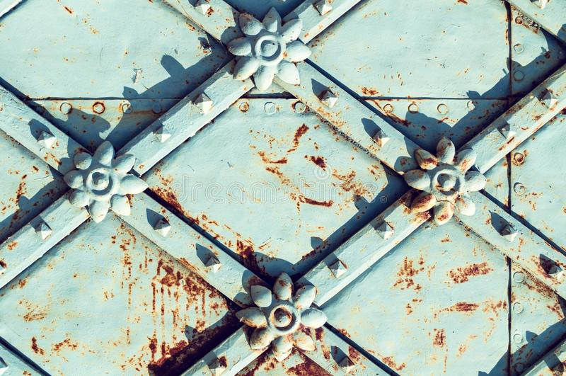 Metal architecture retro background. Vintage metal blue surface with rusty architectural details in the form of flowers stock photo