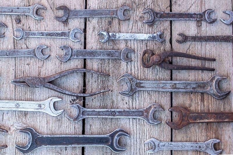 Metal as ferramentas oxidadas da chave que encontram-se em uma tabela de madeira preta Martelo, formão, serrote, chave do metal G fotografia de stock