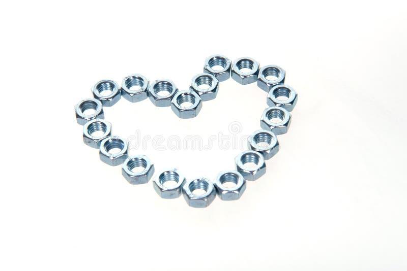 Metal as porcas apresentadas na forma de um coração em um fundo branco fotos de stock