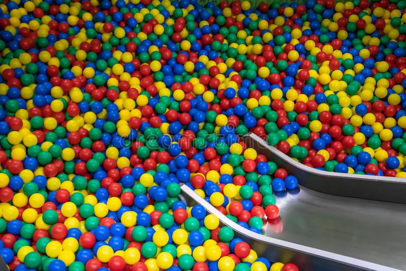 Metal baby slide going down to the pool with many colored balls in the kids playing room.  royalty free stock image