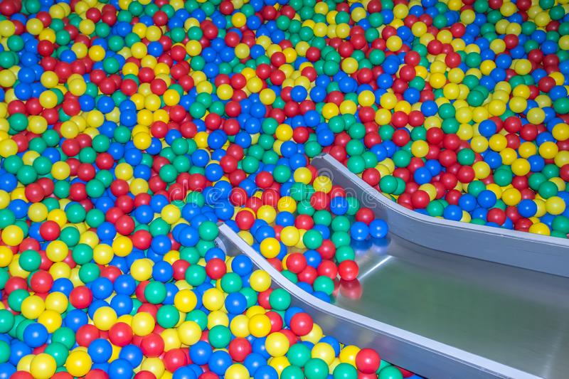 Metal baby slide going down to the pool with many colored balls in the kids playing room.  stock images