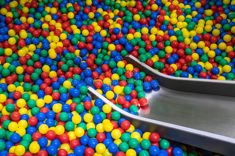 Metal baby slide going down to the pool with many colored balls in the kids playing room.  stock image