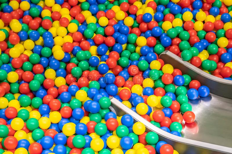 Metal baby slide going down to the pool with many colored balls in the kids playing room.  royalty free stock photos