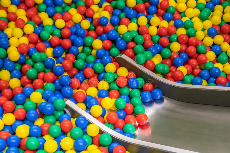 Metal baby slide going down to the pool with many colored balls in the kids playing room.  stock photography
