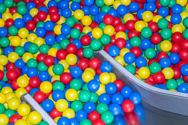 Metal baby slide going down to the pool with many colored balls in the kids playing room.  stock photo