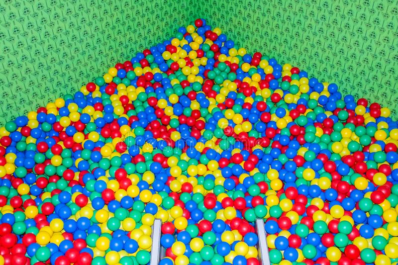 Metal baby slide going down to the pool with many colored balls in the kids playing room.  stock photos