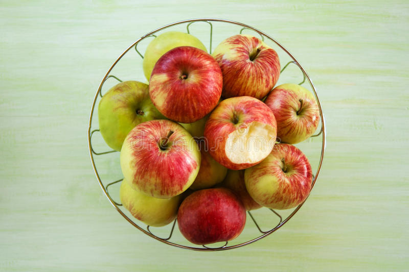 Metal a bacia com as maçãs verdes, amarelas e vermelhas e a uma maçã mordida no fundo de madeira verde imagens de stock
