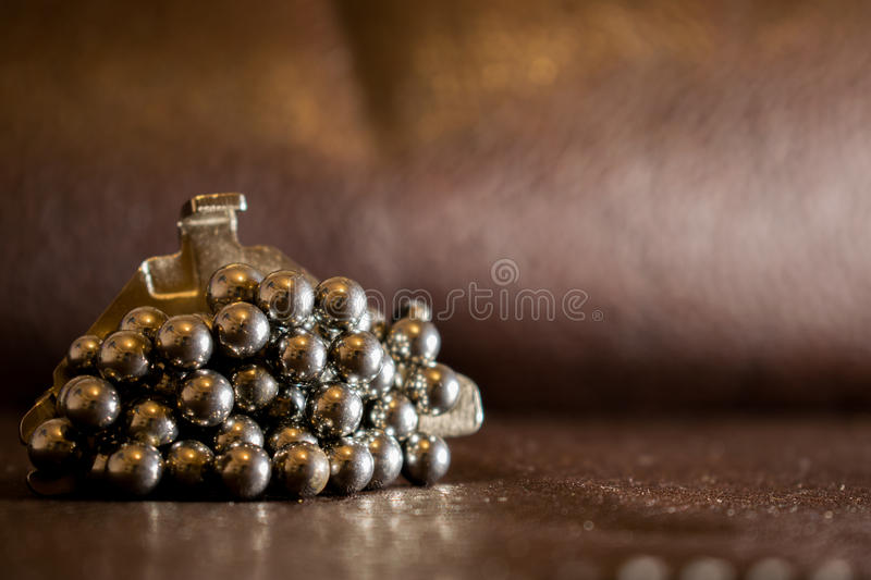 The metal balls from the bearing are stuck to the neodymium magnet, which lies on the leather surface of brown color. royalty free stock photography
