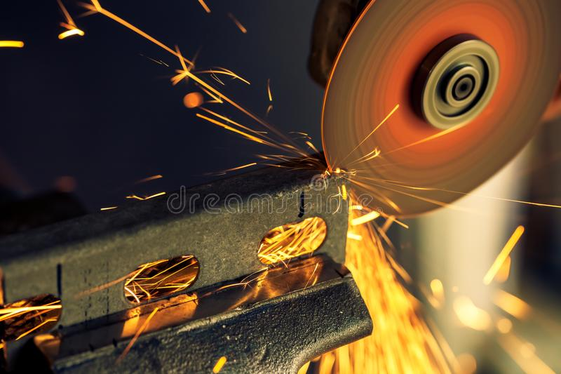 Metal bar being cut with electric grinder with spark flying, selective focus royalty free stock photography