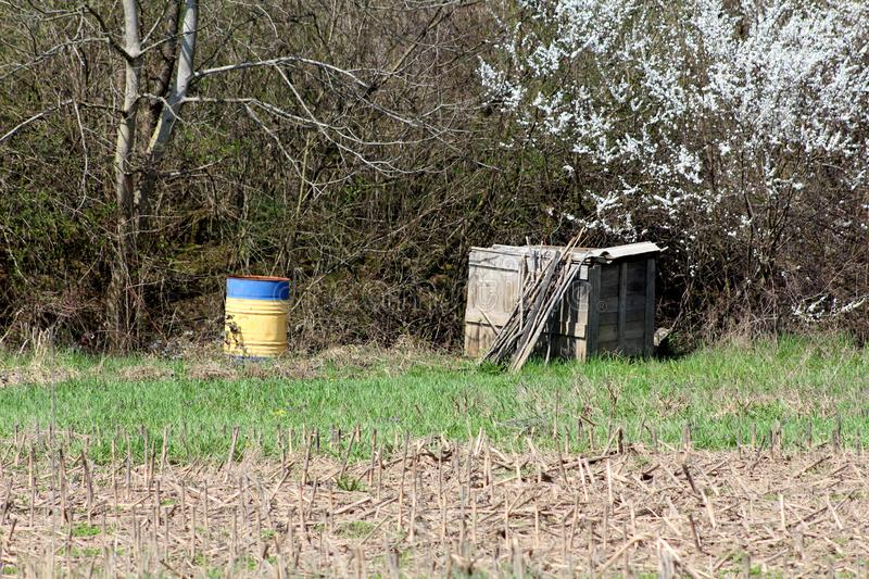 Metal barrel used for storing rain water next to improvised wooden box used as compost pile surrounded with grass and cornfield. Metal barrel used for storing royalty free stock photos