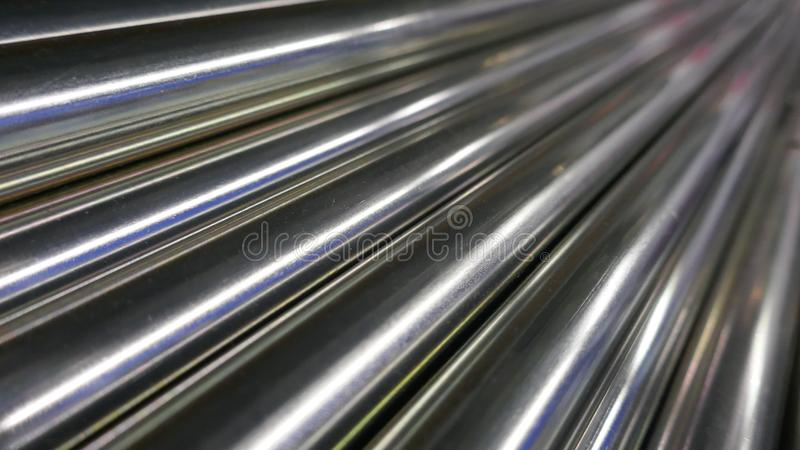 Metal bars, chrome plated and glossy, arranged diagonally royalty free stock photos