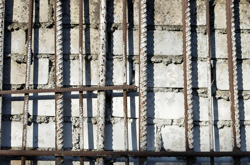 Metal bars, fittings on the background of a white brick wall. On concrete masonry stock images