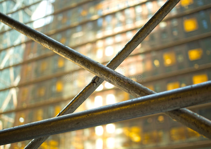 Metal bars in front of a glass building with yellow glowing windows royalty free stock photos