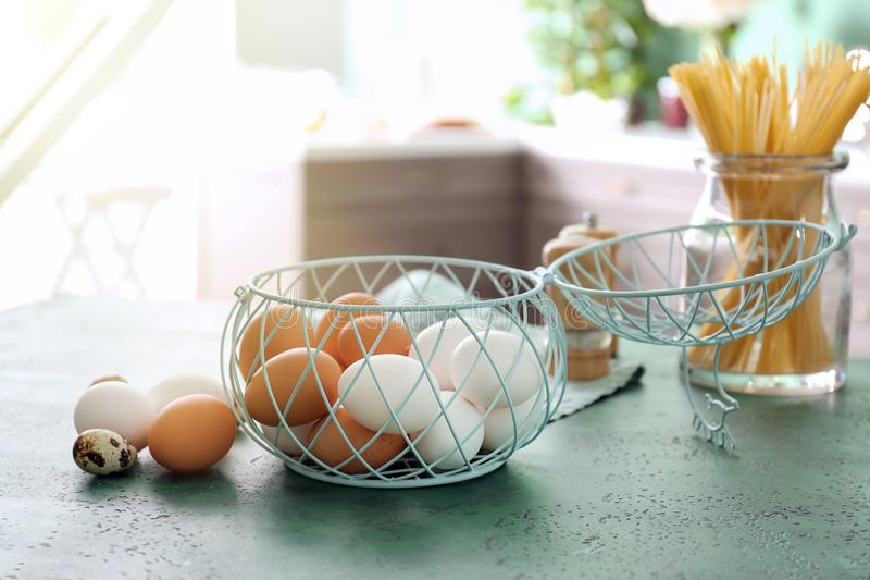 Metal basket with chicken eggs on kitchen table stock image