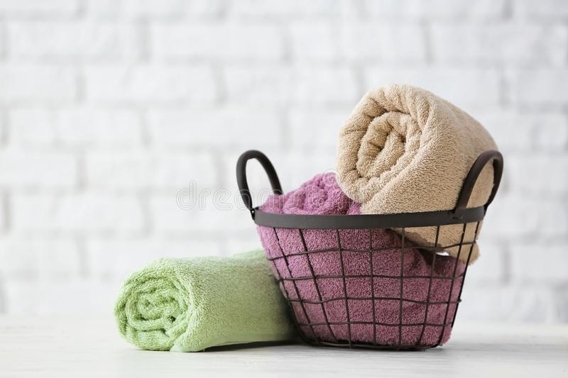 Metal basket with clean soft towels on white table royalty free stock photos