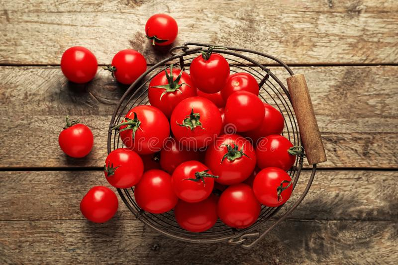 Metal basket with fresh cherry tomatoes on wooden background royalty free stock photo