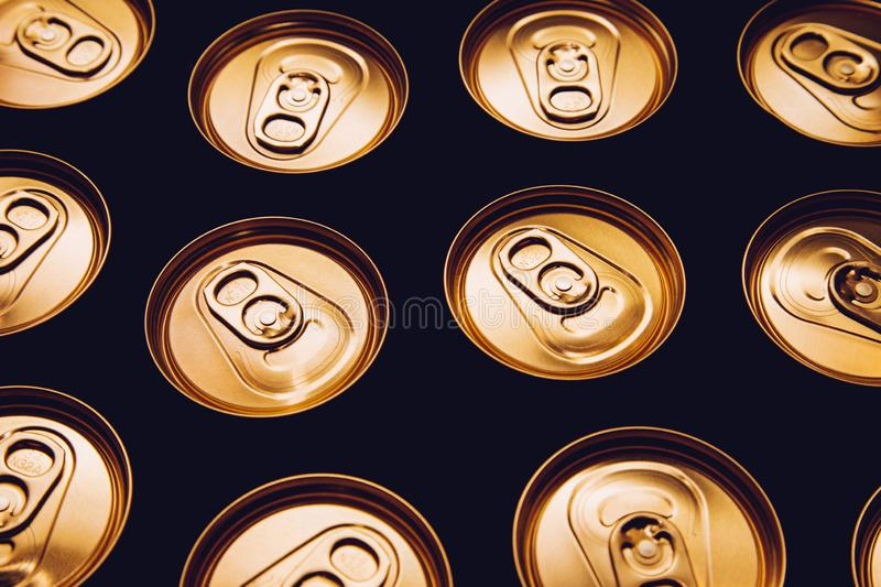 Metal beer cans background black gold row royalty free stock image