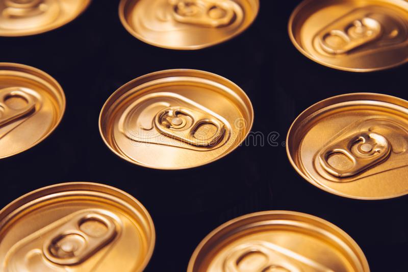 Metal beer cans background black gold row royalty free stock photo