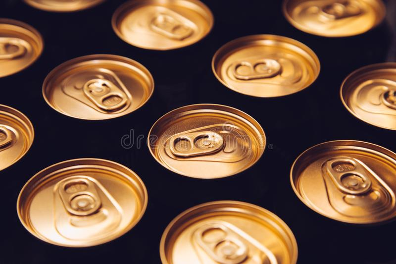 Metal beer cans background black gold row stock photos