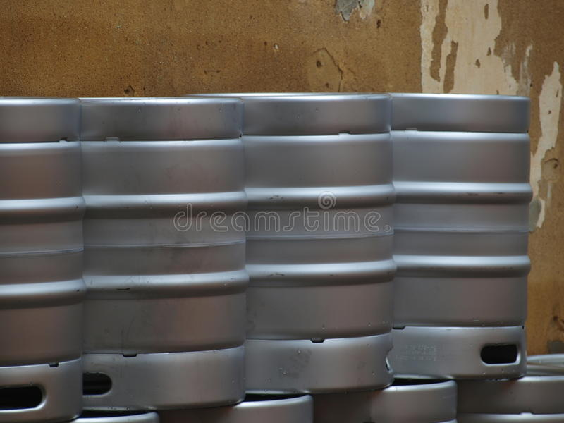 Metal Beer Kegs. Beer kegs are double-stacked along an old plaster wall. The storefront is now gutted, open air and made into an old fashioned beer garden. The stock photography