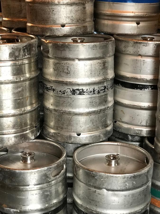 Metal Beer Kegs Stacked in a Vertical View. Many generic, metal beer kegs are shown stacked in a vertical view at a brewery royalty free stock image
