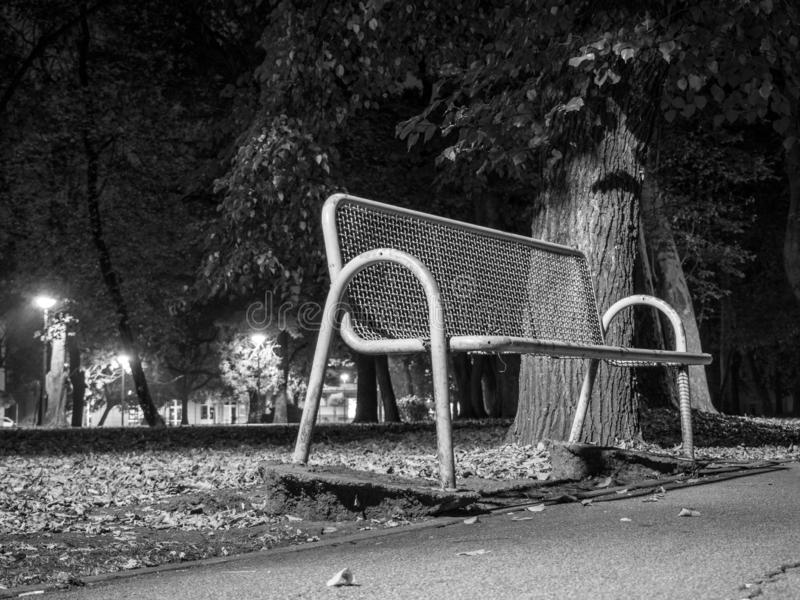 Metal bench in park at night. October, leaves, autumn stock image