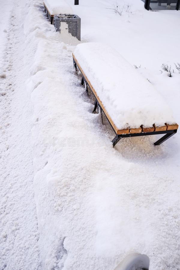 Metal bench with a wooden seat covered with snow stock photos