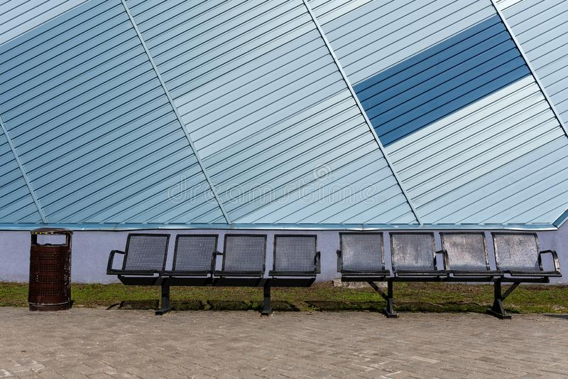 Metal benches at modern buildings facade with blue and silver lines - image stock image